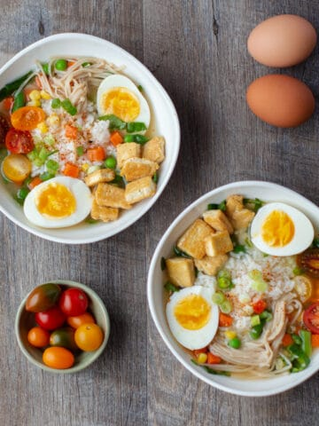 2 white bowls with miso power breakfast, pinch bowl of tomatoes and 2 eggs in shell