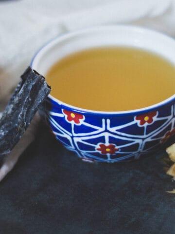 Dashi broth in bowl with dried shiitake, kombu and bonito flakes