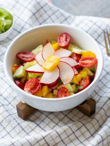 chopped rainbow veggie salad in white bowl