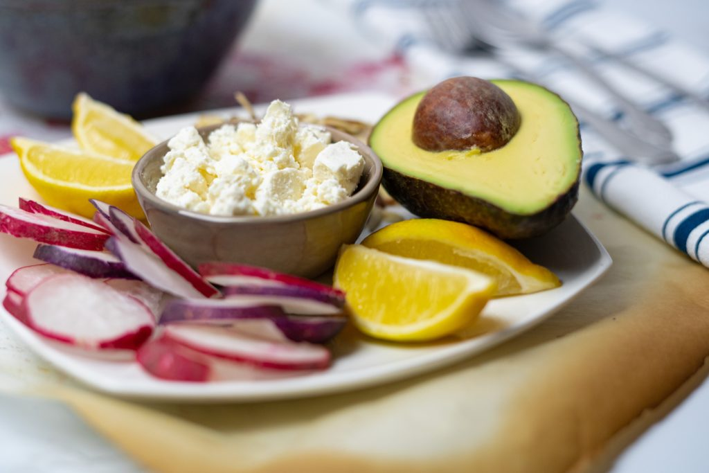 plate with avocado, radish, lemon and feta