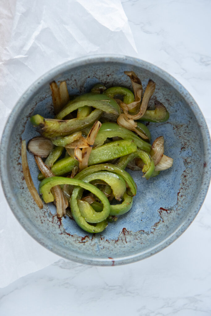 sauted green peppers and onions in blue bowl