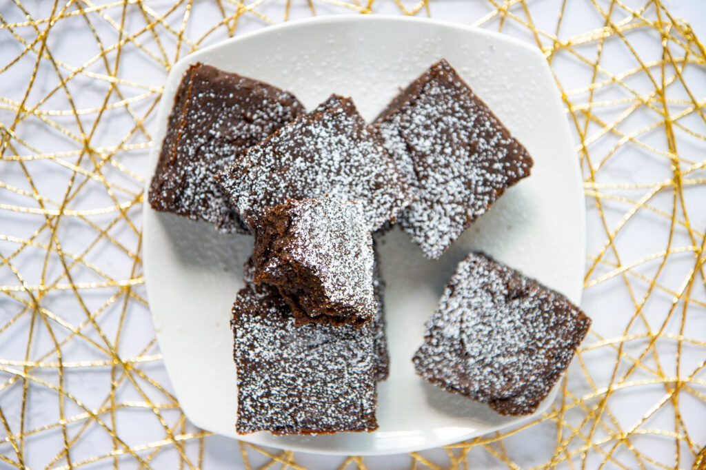 Plate of pumpkin spice brownies with powdered sugar