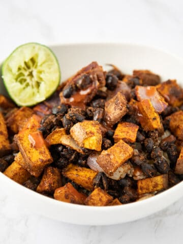 Bowl of sweet potatoes, black beans, red onion and rice.