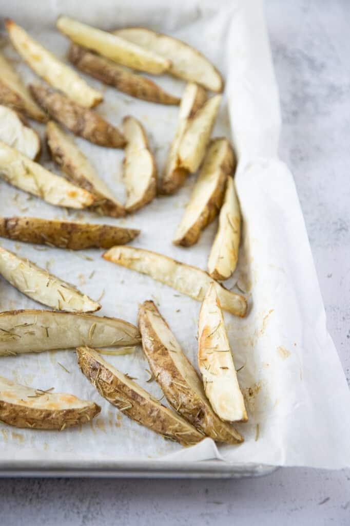 rosemary potato wedges on a baking sheet