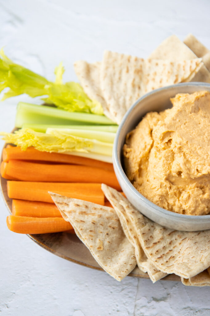 buffalo hummus on a platter with vegetables and pita bread