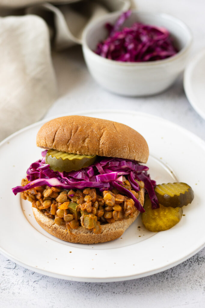 sloppy joe on a bun with pickles and cabbage