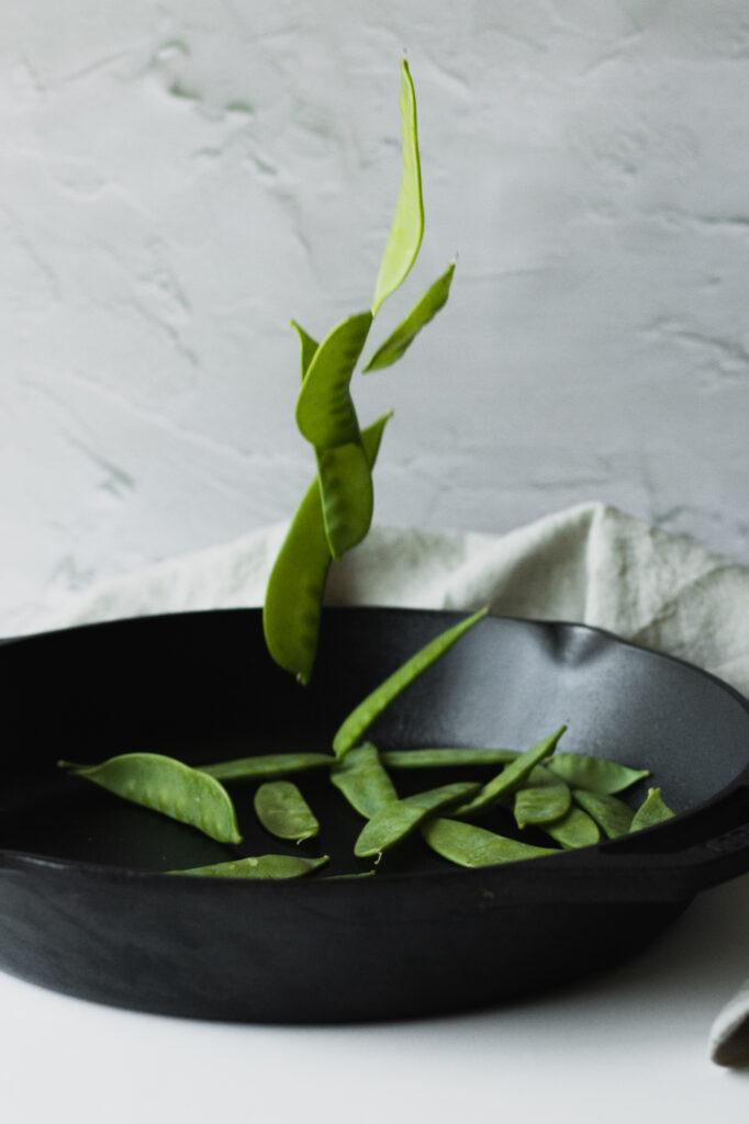 snow peas falling into a cast iron pan