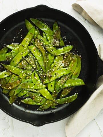 maple sriracha snow peas in a cast iron pan