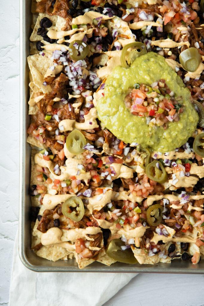 BBQ jackfruit nachos on a baking sheet